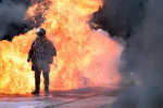 A fire bomb explodes behind a riot police squad