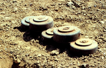 970710-N-2240H-004 Five M15 anti-tank land mines are stacked for destruction at a demolition site on Naval Station Guantanamo Bay, Cuba, in this July 10, 1997, file photo.  Anti-personnel and anti-tank land mines on the U.S. side of the fence separating Communist Cuba and the U.S. Naval Base at Guantanamo Bay are being removed in accordance with the Presidential Order of May 16, 1996.  Approximately 50,000 land mines were placed in the buffer zone between Communist Cuba and Guantanamo Bay beginning in 1961 as a result of the Cold War. The land mines are being replaced by motion and sound sensors to detect any incursion onto the base.  DoD photo by Petty Officer 1st Class Ronald L. Heppner, U.S. Navy.