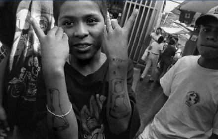 Despite his young age, this Salvadoran boy displays the gang signs for Dieciocho, one of the two predominant gangs in El Salvador.