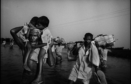 People return to their villages in the floodwater in Bihar, India on September 30, 2008. The flood of the Kosi River caused a slow but steady flow of water, which was relatively shallow, but tens of kilometers wide covering local infrastructure entirely.