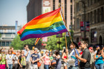 Marchers in the 2013 Twin Cities Pride parade carry rainbow flags as spectators watch along Hennepin Avenue in Minneapolis, Minnesota.