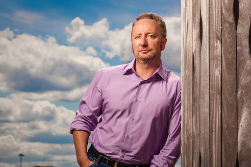 Caucasian man in purple shirt leaning against wood wall outdoors on blue-skyed day with clouds.