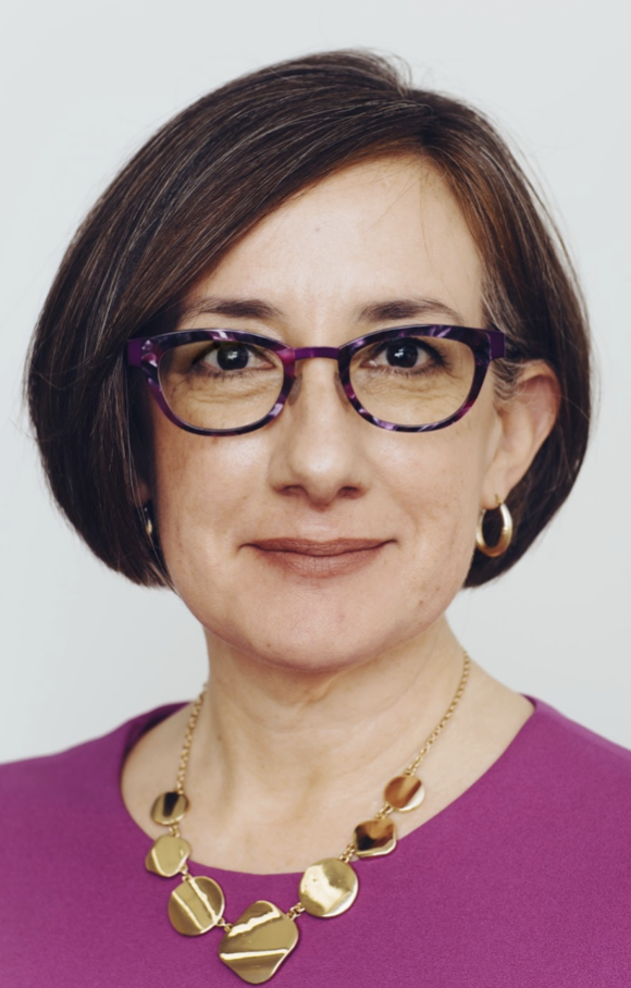 White woman with glasses, short brown hair, ornate necklace, magenta shirt, and round earrings.