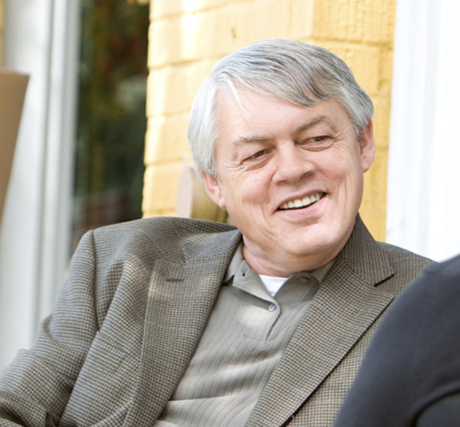 White man, gray hair, green-gray collared shirt with a striped blazer.