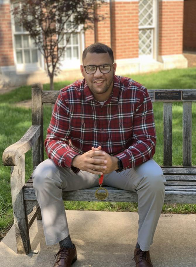 Black man wearing a plaid button-down shirt, grey pants, glasses.