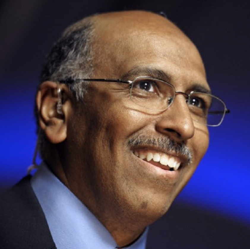 Black man with glasses, mustache, blue collared shirt, navy blue blazer, smiling