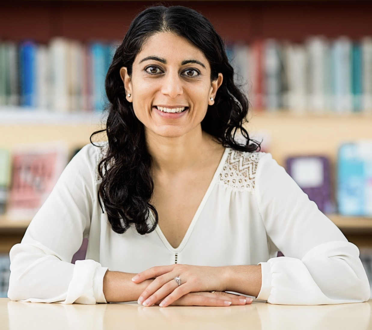 Woman with dark curly hair, white shirt, smiling, books in the background