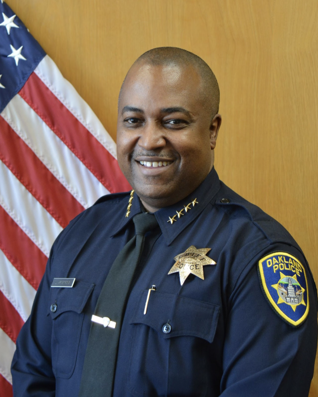 Black police officer, in uniform, smiling. American flag in the background