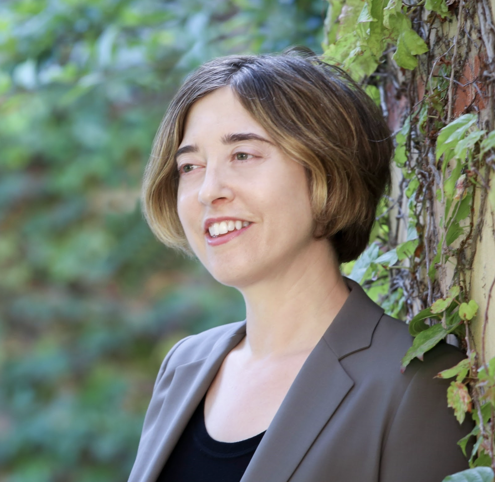 White woman smiling. She is wearing grey blazer and a black shirt. Tree in the background