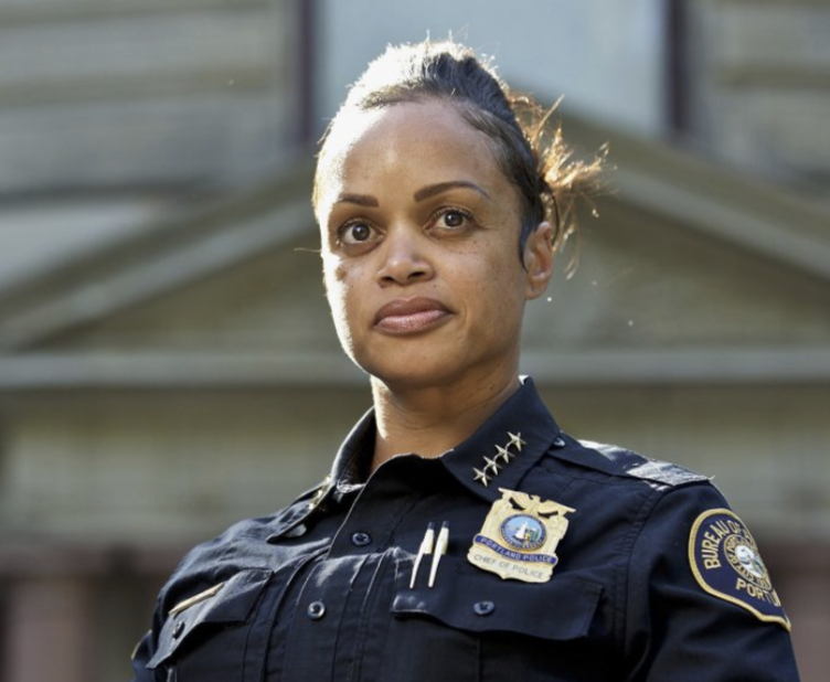 Black woman in a navy blue police uniform. Background is a blurry building.